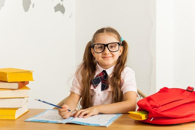 Schoolmeisje met zonnebril met veel boeken op school