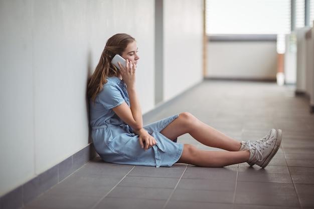 Schoolmeisje praten op mobiele telefoon in gang