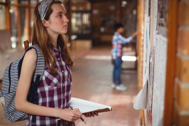 Schoolmeisje prikbord in gang lezen
