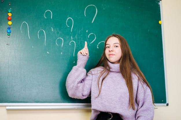 Schoolmeisje schreef vraagtekens met krijt op een schoolbord in de klas van de school. vragen zonder antwoorden.