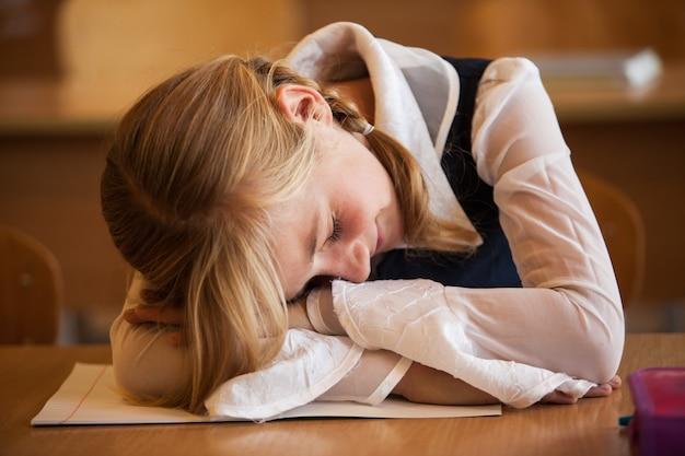 Schoolmeisje slaapt op het bureau tijdens de saaie les