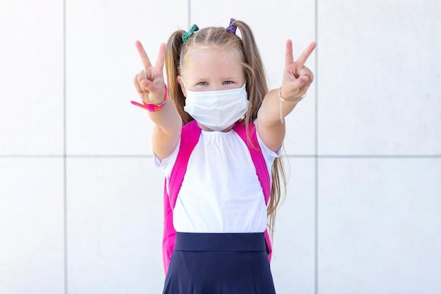 Schoolmeisje staat met een rugzak in een beschermend medisch masker. toont vrede
