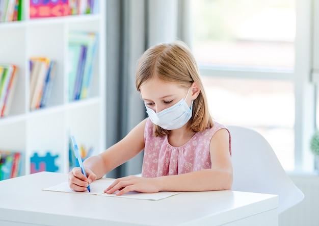 Schoolmeisje studeert in de klas met gezichtsmasker tijdens pandemie