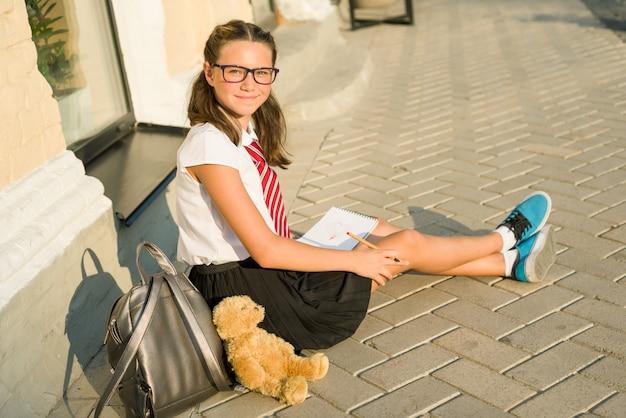 Schoolmeisje tiener schrijft in een notitieblok