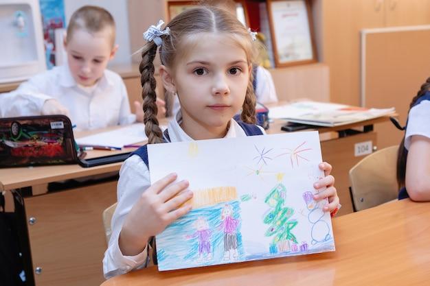 Schoolmeisje toont een tekening aan het bureau in de klas tijdens de les