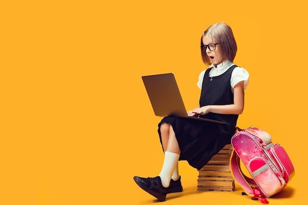 Schoolmeisje van volledige lengte in shock zit op de stapel boeken en kijkt naar het onderwijsconcept voor laptops