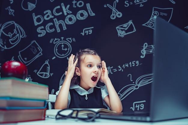 Schoolmeisje zit aan de tafel met laptopboeken en een schoolbord met schoolformules op achtergrond w...