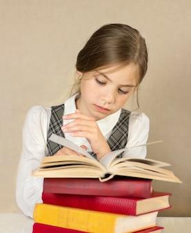 Schoolmeisje zit met een open boek en leest