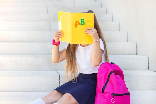 Schoolmeisje zit op de trap met een rugzak en een leerboek bedekt haar gezicht