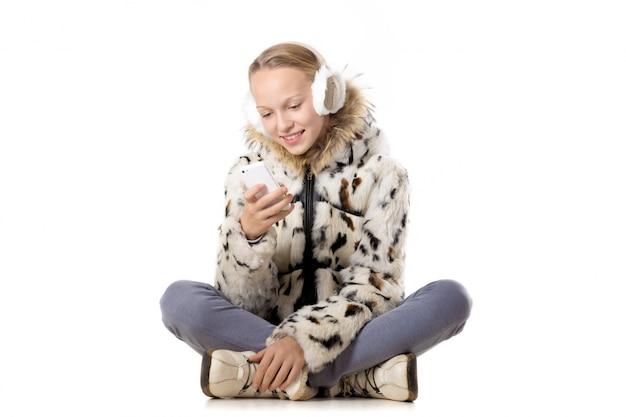 Schoolmeisje zit op de vloer met haar smartphone