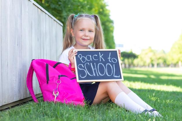 Schoolmeisje zit op het gras, schoolrugzak. houdt een bord in zijn handen met het opschrift terug naar school