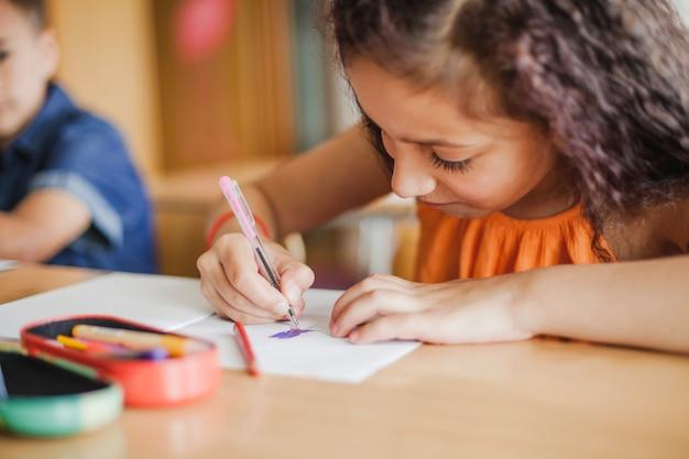 Schoolmeisje zitten aan tafel tekening