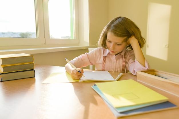Schoolmeisje, zittend aan tafel met boeken en schrijven in notitieblok