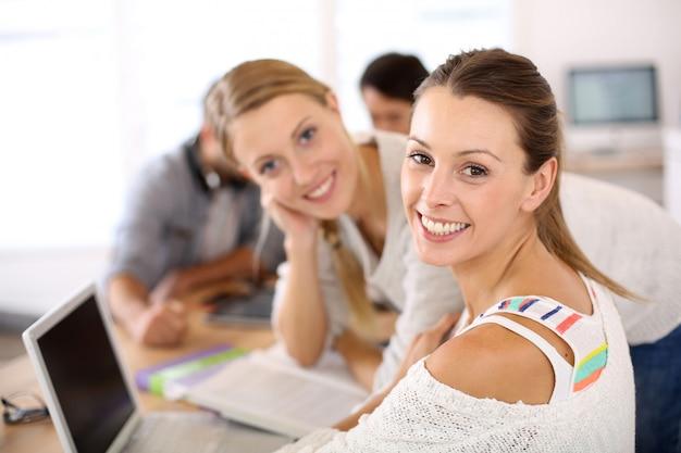 Schoolmeisjes die in klasse op laptop computer bestuderen