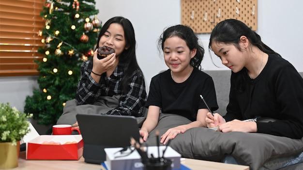Schoolmeisjes die thuis samen online les studeren.