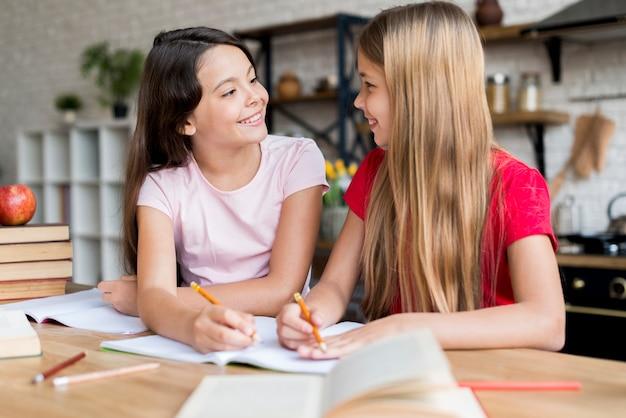 Schoolmeisjes huiswerk maken en naar elkaar kijken