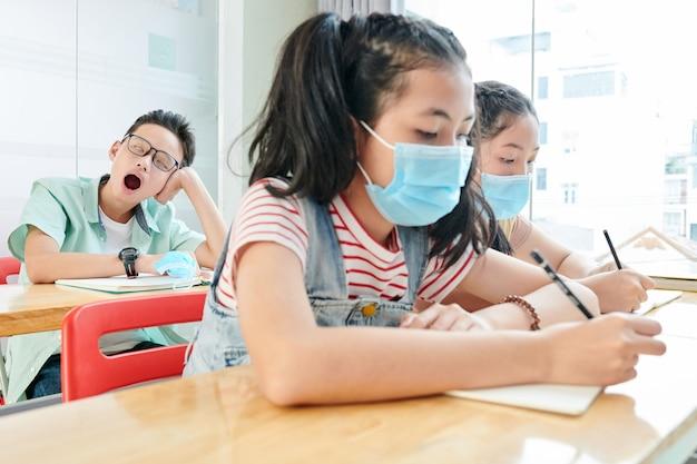 Schoolmeisjes in medische maskers die in voorbeeldenboeken schrijven als hun klasgenoot geeuwt