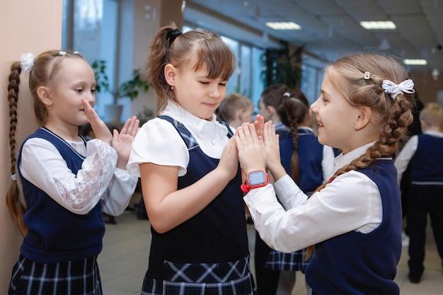 Schoolmeisjes in uniform spelen patty-cake tijdens de pauze. school basisonderwijs. selectieve aandacht.