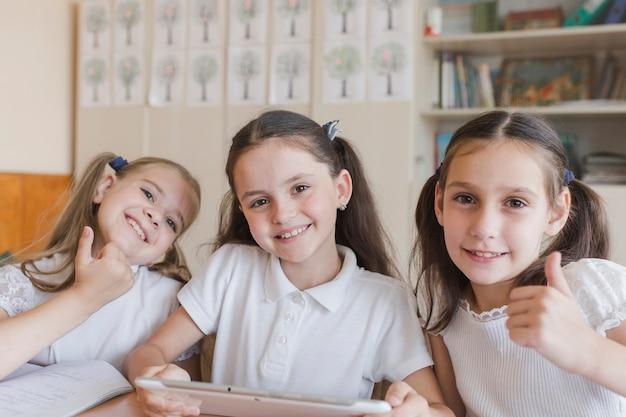 Schoolmeisjes met duim-omhoog gebaren van de tablet