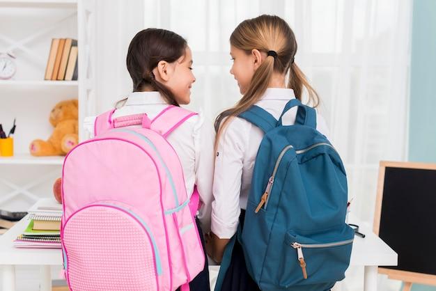 Schoolmeisjes met rugzakken kijken naar elkaar