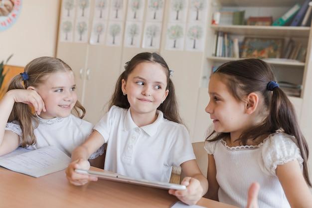 Schoolmeisjes met tablet die met elkaar spreken
