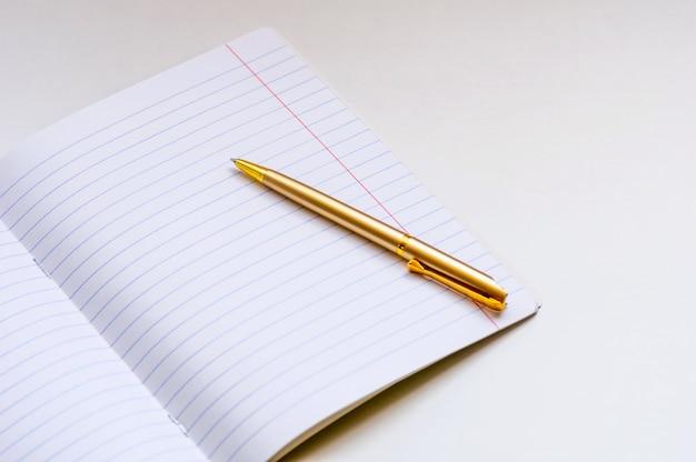 Schoolnotitieboekje en gouden ballpoint op een lichte achtergrond.