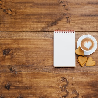 Schoolnotitieboekje en koffiemok op een houten achtergrond