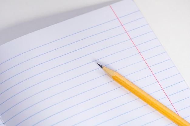Schoolnotitieboekje en potlood op een lichte achtergrond.