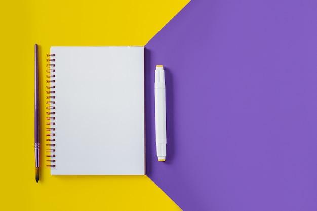 Schoolnotitieboekje op gele en purpere, spiraalvormige blocnote op een lijst. bovenaanzicht achtergrond met copyspace. kantoor kladblok plat lag.