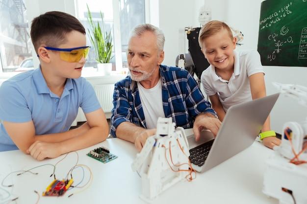 Schoolonderwijs. aardige, aangename man die naar zijn leerling kijkt terwijl hij hem uitlegt over moderne technologie
