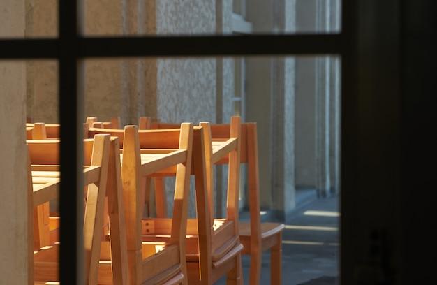 Schoolscène met stapel studeertafels en stoelen houden in veranda in oud schooltijdgeheugen