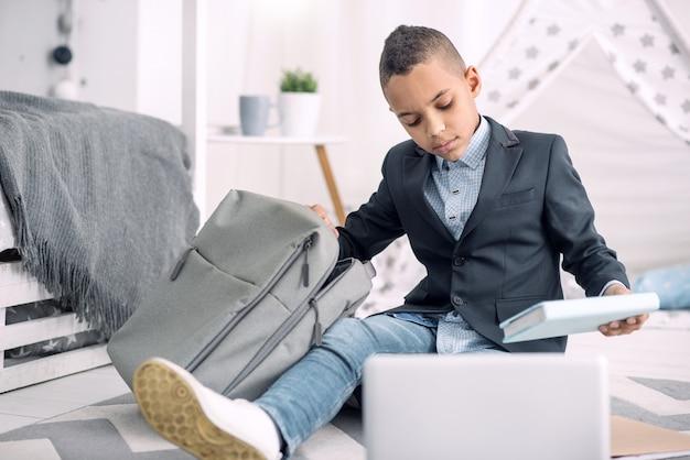 Schoolspullen. triest afro-amerikaanse jongen zittend op de vloer terwijl hij een boek uit schooltas haalt
