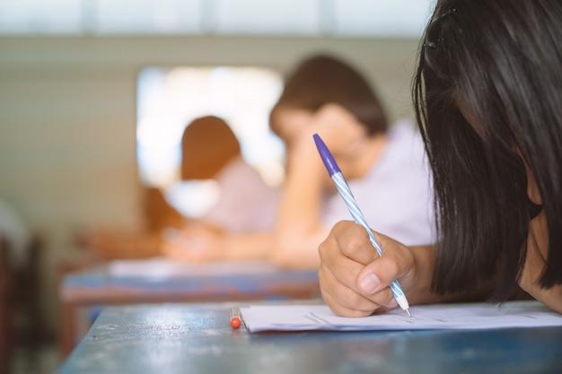 Schoolstudenten die examen het schrijven antwoord in klaslokaal met spanning nemen
