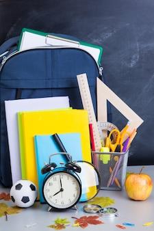 Schooltas en service in de buurt van het lerarenbord