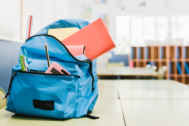 Schooltas met verschillende hulpmiddelen op bureau
