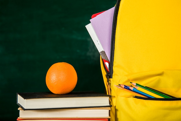 Schooltas, stapel boeken en oranje