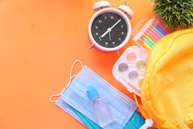 Schooltas voor studenten met gezichtsmasker en ontsmettingsmiddel op oranje