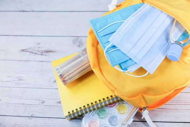 Schooltas voor studenten met ontsmettingsmiddel, een gezichtsmasker.