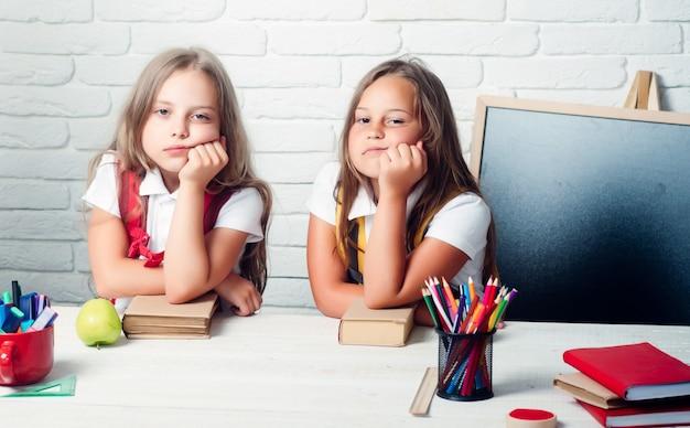 Schooltijd van meisjes. terug naar school en thuisonderwijs. vriendschap van kleine zusjes in de klas op kennisdag. verveelde schoolkinderen bij les.
