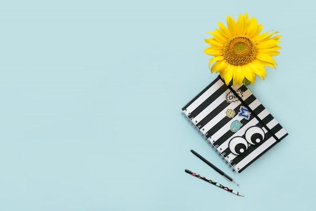 Schooltoebehoren gestreept zwart-wit notitieboekje, pen, pencile en zonnebloem