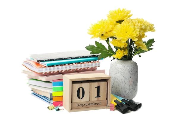 Schooltoebehoren, houten kalender en bloemen die op wit worden geïsoleerd