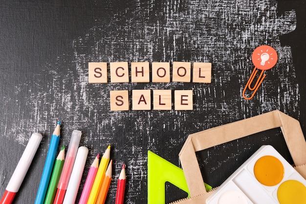 Schoolverkoop met trendy schaduw en verschillende benodigdheden op bord.