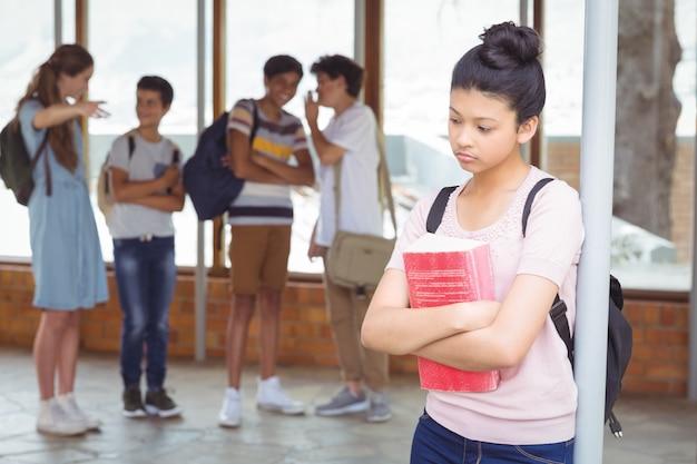 Schoolvrienden die een verdrietig meisje in gang pesten