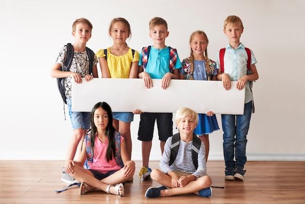 Schoolvrienden met wit aanplakbiljet