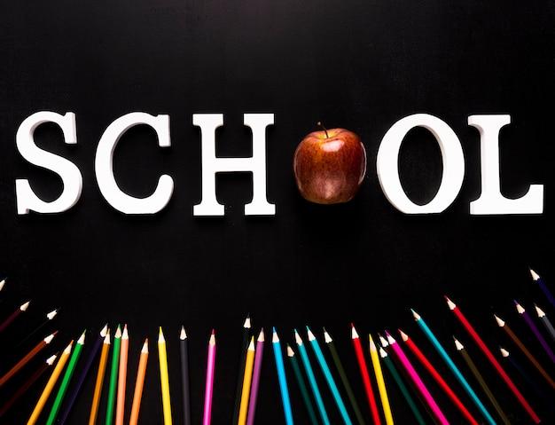 Schoolwoord en uitgestrooide kleurenpotloden op zwarte achtergrond