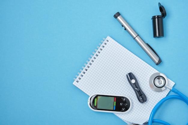 Schoon blok met veer, stethoscoop, glucosemeter, lancet en spuitpen met insuline op een blauwe achtergrond, daibet-dagconcept, diabetesdiagnose