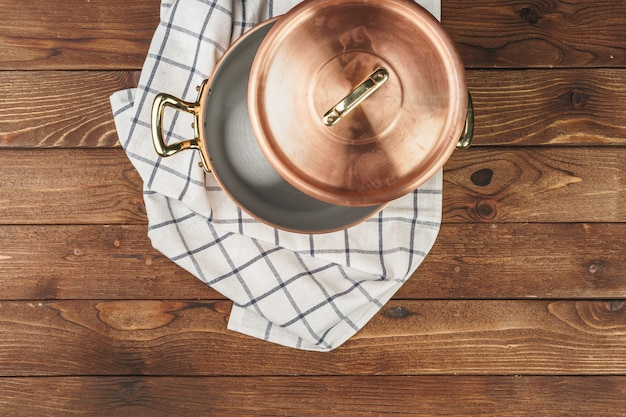 Schoon glanzend koperen keukengerei op een houten bord