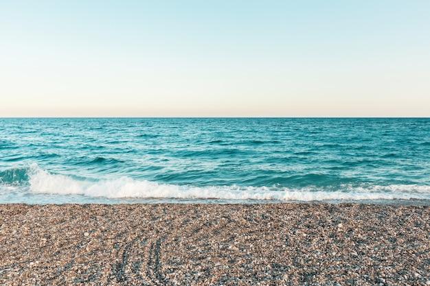 Schoon zandstrand met blauwe oceaan en heldere hemel