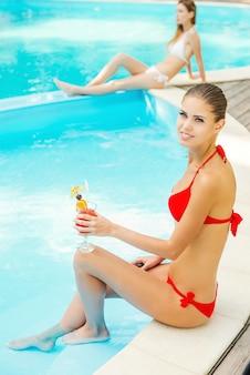 Schoonheden bij het zwembad. bovenaanzicht van twee mooie jonge vrouwen in bikini ontspannen bij het zwembad