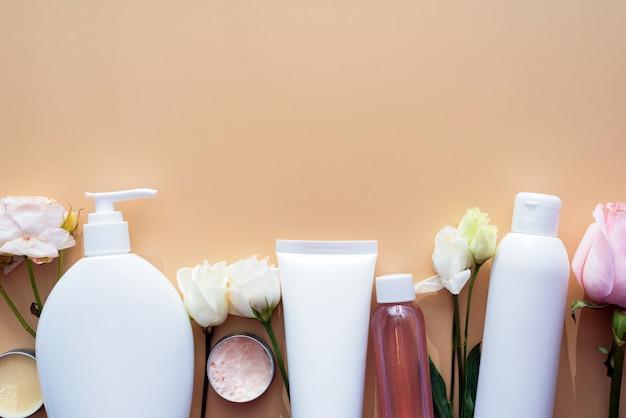 Schoonheid achtergrond met cosmetische gezichtsproducten en bloemen op pastel beige bureaubladachtergrond.